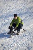 Junge Sledding unten Hügel im Winter Stockbilder