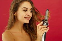 Junge smileyfrau, die gelocktes Haar durch Trick über rotem Hintergrund herstellt Lizenzfreies Stockfoto