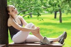 Junge sorglose blonde Frau, die auf Bank im grünen Park sitzt Lizenzfreie Stockbilder