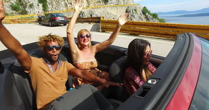 Junge sorglose Leute an den Sommerferien, die den Spaß fährt im roten Kabriolett haben stock video