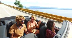 Junge sorglose Leute an den Sommerferien, die den Spaß fährt im roten Kabriolett haben stock video footage