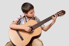 Junge spielt die Akustikgitarre stockbild