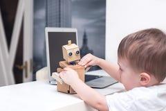 Junge spielt mit dem Roboter auf einer weißen Tabelle zu Hause Lizenzfreies Stockbild