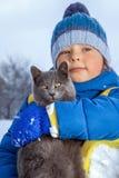 Junge spielt mit einer Katze draußen sich konzentrieren auf Katze Lizenzfreies Stockbild