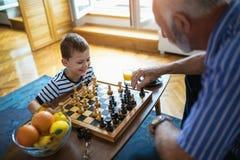 Junge spielt Schach mit seinem Großvater Stockfotos