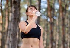 Junge Sport-Frauen-Trinkwasser während des Laufens in schöne wilde Kiefer Forest Active Lifestyle Concept Lizenzfreies Stockfoto