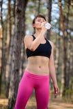 Junge Sport-Frauen-Trinkwasser während des Laufens in schöne wilde Kiefer Forest Active Lifestyle Concept Stockfotografie