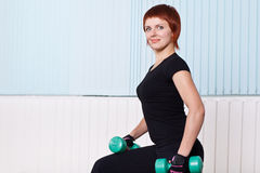 Junge Sportfrau mit Dumbbells Stockfotografie