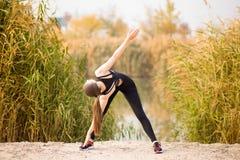Junge sportive Frau, die Übungen im Herbst tut Sportlerin, die ihren Körper ausdehnt stockbilder