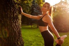 Junge sportive Frau, die Übungen im Sommerpark tut Sportlerin, die ihre Beine bereitstehen Baum ausdehnt Gesunder Lebensstil lizenzfreies stockbild