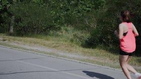 Junge sportive Frau mit dem Cellulite, der in Park läuft Attraktives Mädchen in der rosa Sportkleidung und in den Kopfhörern, die stock video footage