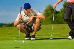Junge sportive Paare, die Golf auf einem Kurs spielen Stockfotos