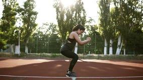 Junge Sportlerin in der Sportkleidung hocken Übung die im Freien Großartiger Brunette im schwarzen T-Shirt und im Legging stock footage