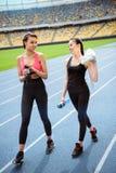 Junge Sportlerinnen mit den Flaschen Wasser gehend auf Laufbahnstadion Lizenzfreie Stockbilder
