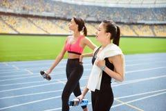 Junge Sportlerinnen mit den Flaschen Wasser gehend auf Laufbahnstadion Stockfoto