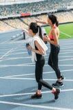 Junge Sportlerinnen mit den Flaschen Wasser gehend auf Laufbahnstadion Lizenzfreies Stockbild