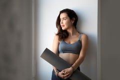 Junge sportliche attraktive Frau, nachdem Yoga geübt worden ist lizenzfreie stockbilder