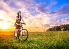 Junge sportliche Frau bei Sonnenuntergang auf einem Fahrrad Sportliches Mädchen auf dem Fahrrad gestoppt, um den Moment bei schön Lizenzfreie Stockfotos