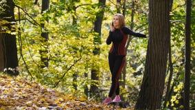 Junge, sportliche Frau, die auf Mobiltelefon am Herbstpark im Freien, schauend mit Himmel spricht Lizenzfreies Stockfoto