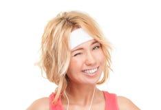 Junge sportliche Frau, die auf weißem Hintergrund blinzelt. Stockfoto