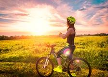 Junge sportliche Frau, die den Sonnenuntergang auf einem Fahrrad aufpasst Sportliches Mädchen auf dem Fahrrad gestoppt, um den Mo Lizenzfreies Stockfoto
