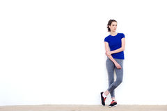 Junge sportliche Frau, die an der weißen Wand anstarrt und sich lehnt Stockfotos