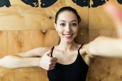Junge sportliche Frau, die ein selfie mit Handy für soziale Netzwerke an der Turnhalle mit den Daumen oben nimmt Stockfotografie