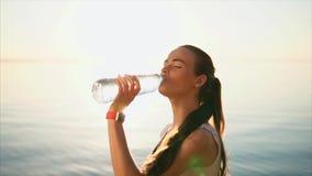 Junge sportliche Frau, die ein Wasser von der Plastikflasche nahe dem Meer trinkt stock video footage