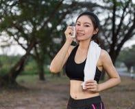 Junge sportliche Frau, die ihren Schweiß mit einem Tuch Achtern liegt und abwischt Stockbild