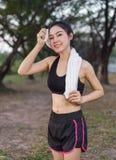 Junge sportliche Frau, die ihren Schweiß mit einem Tuch Achtern liegt und abwischt Lizenzfreie Stockfotografie