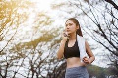 Junge sportliche Frau, die ihren Schweiß mit einem Tuch Achtern liegt und abwischt Stockfotos