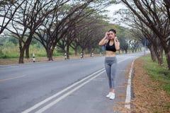 Junge sportliche Frau, die ihren Schweiß mit einem Tuch Achtern liegt und abwischt Stockbilder