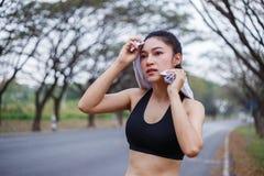 Junge sportliche Frau, die ihren Schweiß mit einem Tuch Achtern liegt und abwischt Stockfoto