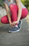 Junge sportliche Frau, die Laufschuhspitzee bevor dem Rütteln im Park im Sonnenschein am schönen Sommertag bindet Stockfoto