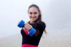 Junge sportliche Frau, die mit dumbells während Eignung worko trainiert Lizenzfreie Stockbilder