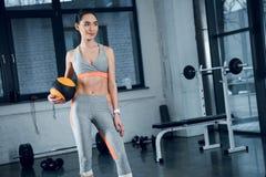 junge sportliche Frau, die mit Mini-pilates Ball steht lizenzfreies stockbild
