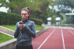 Junge sportliche Frau, die Musik unter Verwendung eines Smartphone hört Lizenzfreie Stockbilder