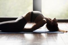Junge sportliche Frau, die oben Matsyasana-Übung, Abschluss tut stockbild