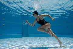 Junge sportliche Frau, die unter Wasser läuft Stockfoto