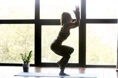 Junge sportliche Frau, die Yoga Eagle-Übung tut stockbild
