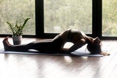 Junge sportliche Frau, die Yoga Matsyasana-Übung tut stockfotografie