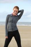 Junge sportliche Frau im Sport statten draußen lächeln aus Stockbild