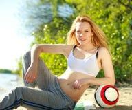 Junge sportliche Frau mit Ball auf dem Strand Lizenzfreies Stockfoto