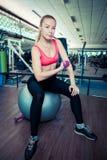 Junge sportliche Frau tun körperliche Bewegungen mit Gewicht auf Sitzball in der Turnhalle Stockfotografie