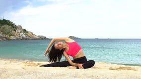 Junge sportliche Frau tut das Ausdehnen von Übung auf dem Strand nahe dem Meer Gesundes aktives Lebensstil-Konzept stock video