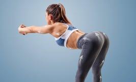 Junge sportliche Frau wärmt Neigungen auf stockfotografie