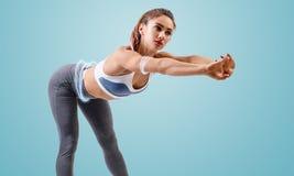 Junge sportliche Frau wärmt Neigungen auf lizenzfreie stockbilder