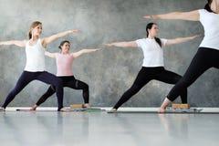 Junge sportliche Frauen, die Yogalektionsstellung in der Übung des Kriegers zwei üben lizenzfreie stockfotos