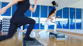 Junge sportliche Frauen, welche die Stepp-Aerobic in der Turnhalle ausbilden stock video