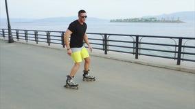 Junge sportliche Mannrollschuhlaufen auf Sommerseeseite stock video footage